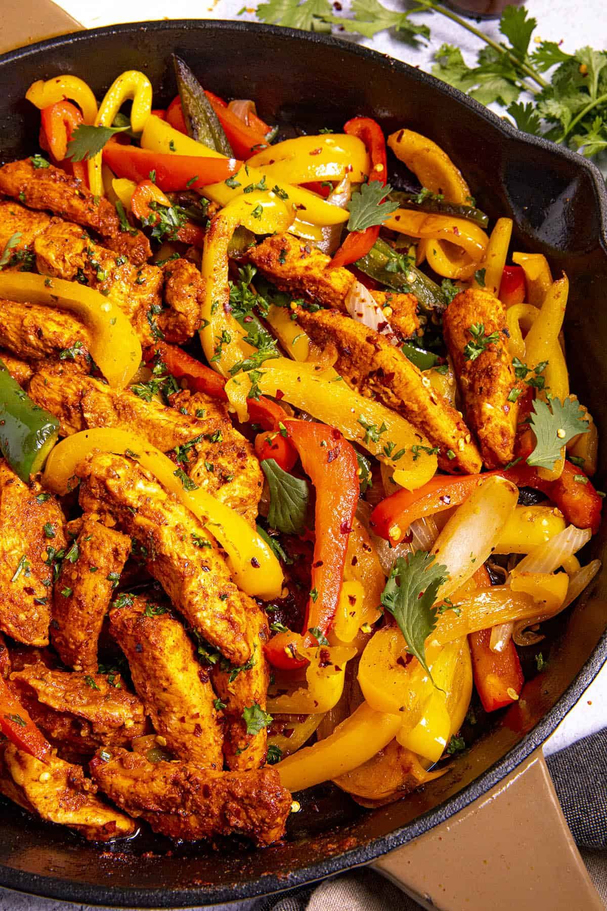 Delicious Chicken Fajitas in a hot pan with lots of garnish