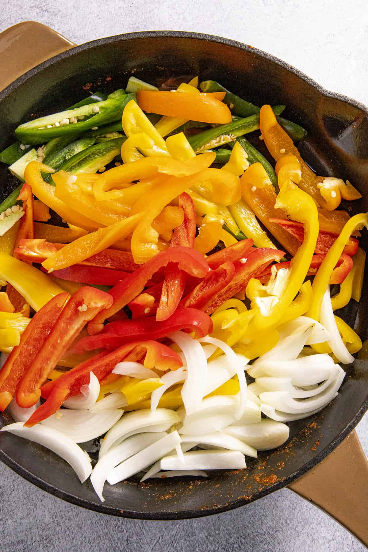 Cooking peppers and onions to make chicken fajitas