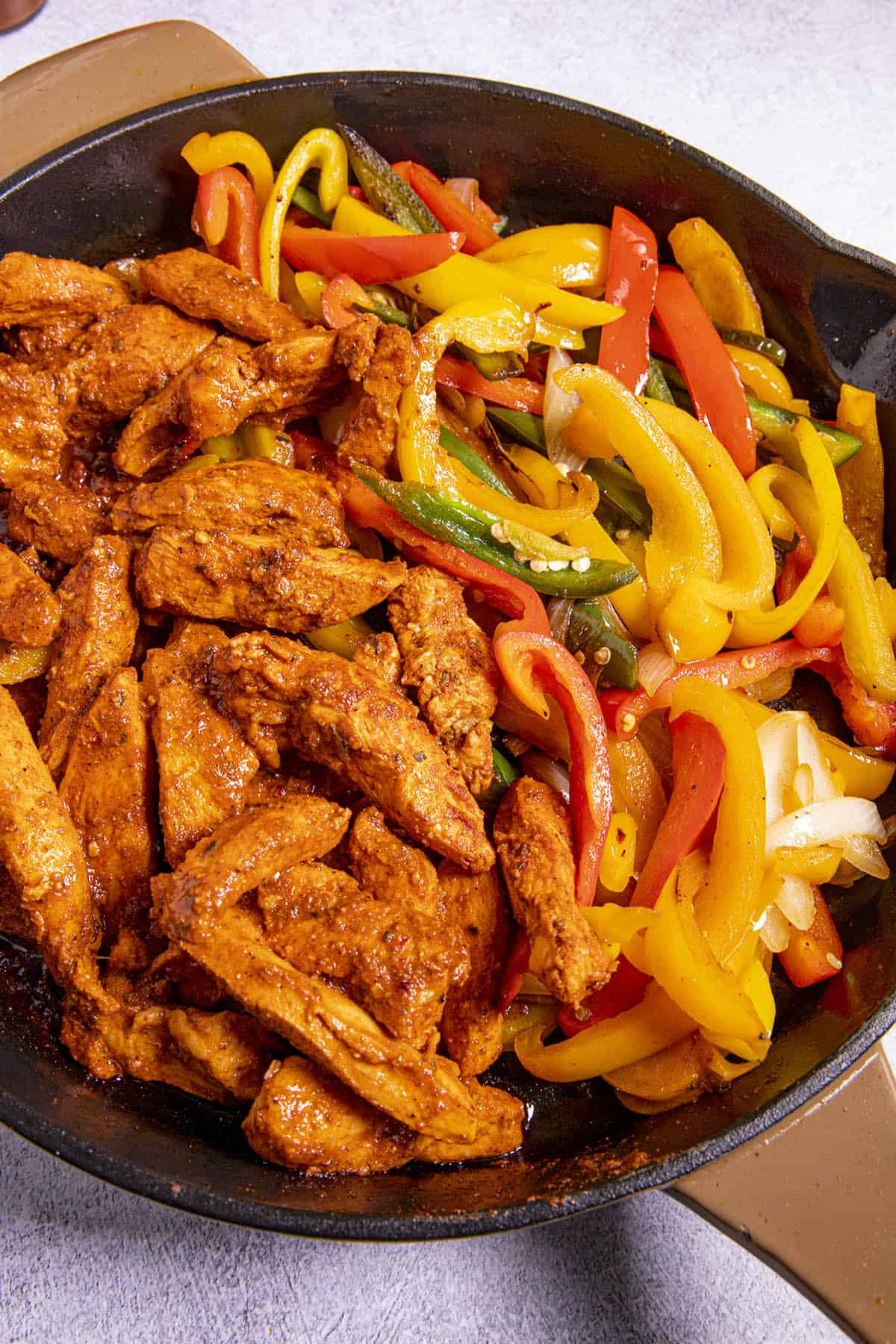 Adding chicken back to pan with the peppers to heat