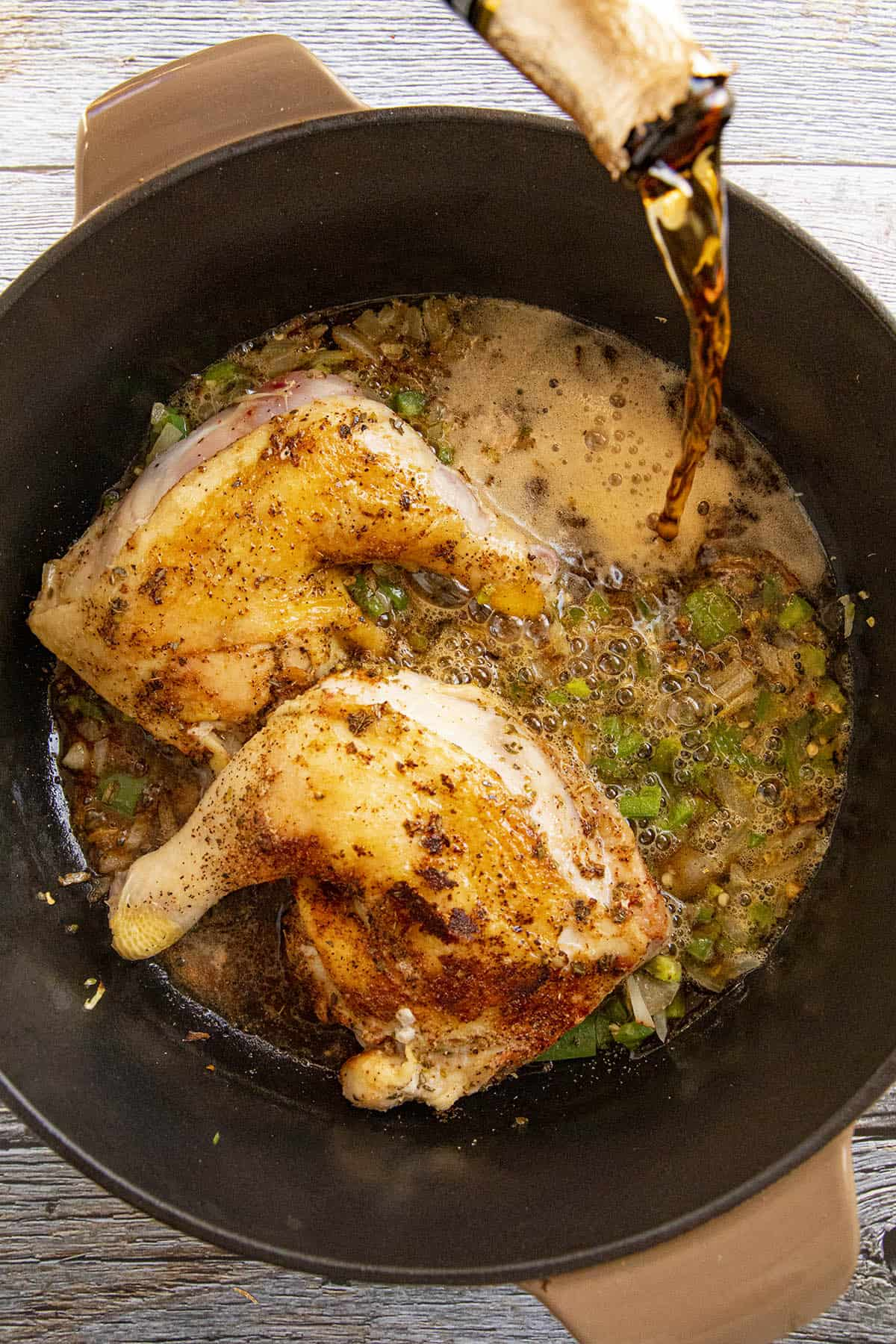 Adding liquid to the pan to braise the chicken