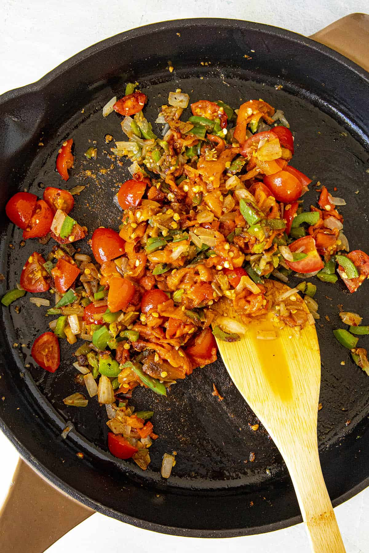 Cooking peppers, onions and tomatoes in a hot pan