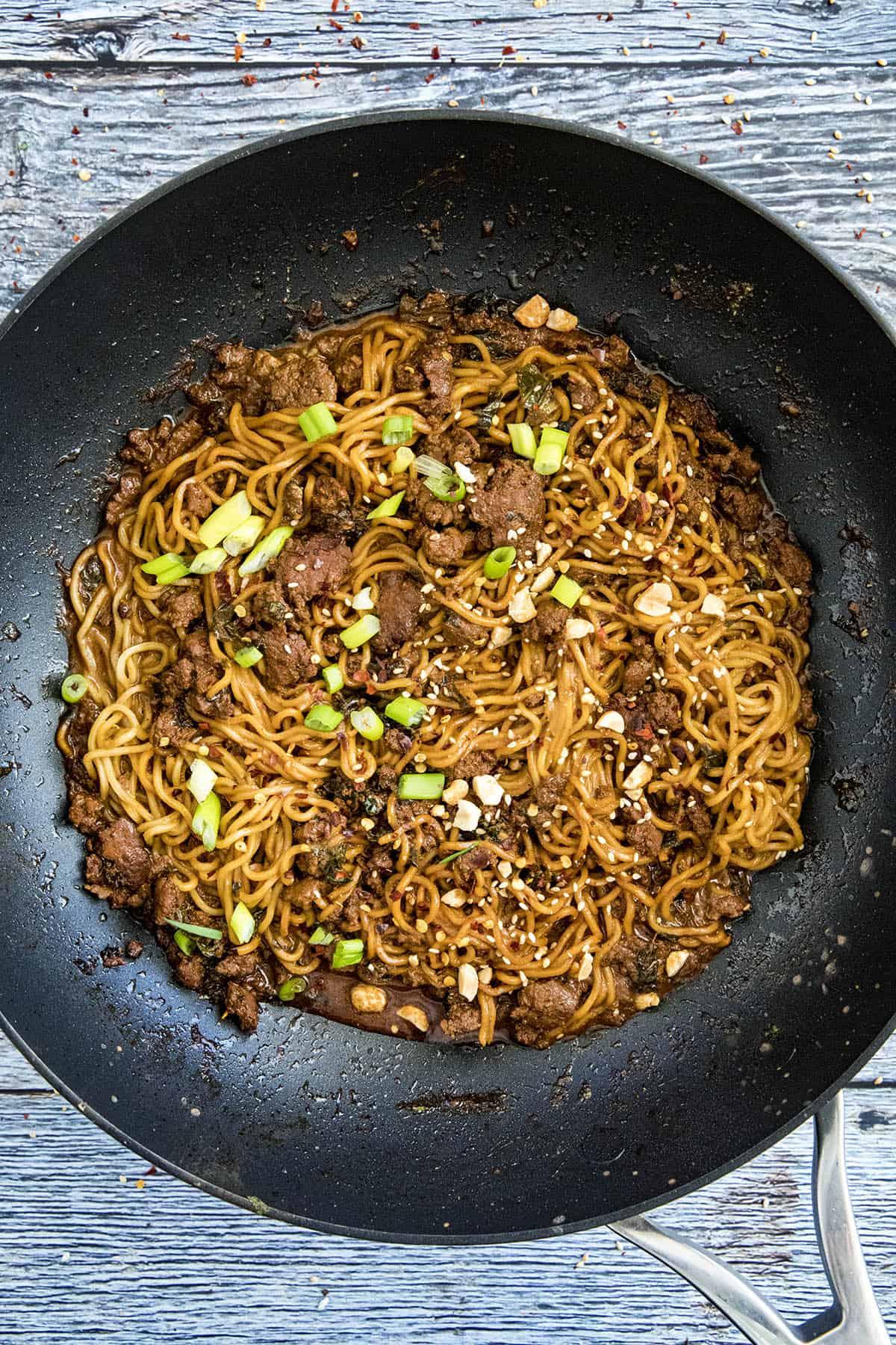 Dan Dan Noodles in a pan with garnish