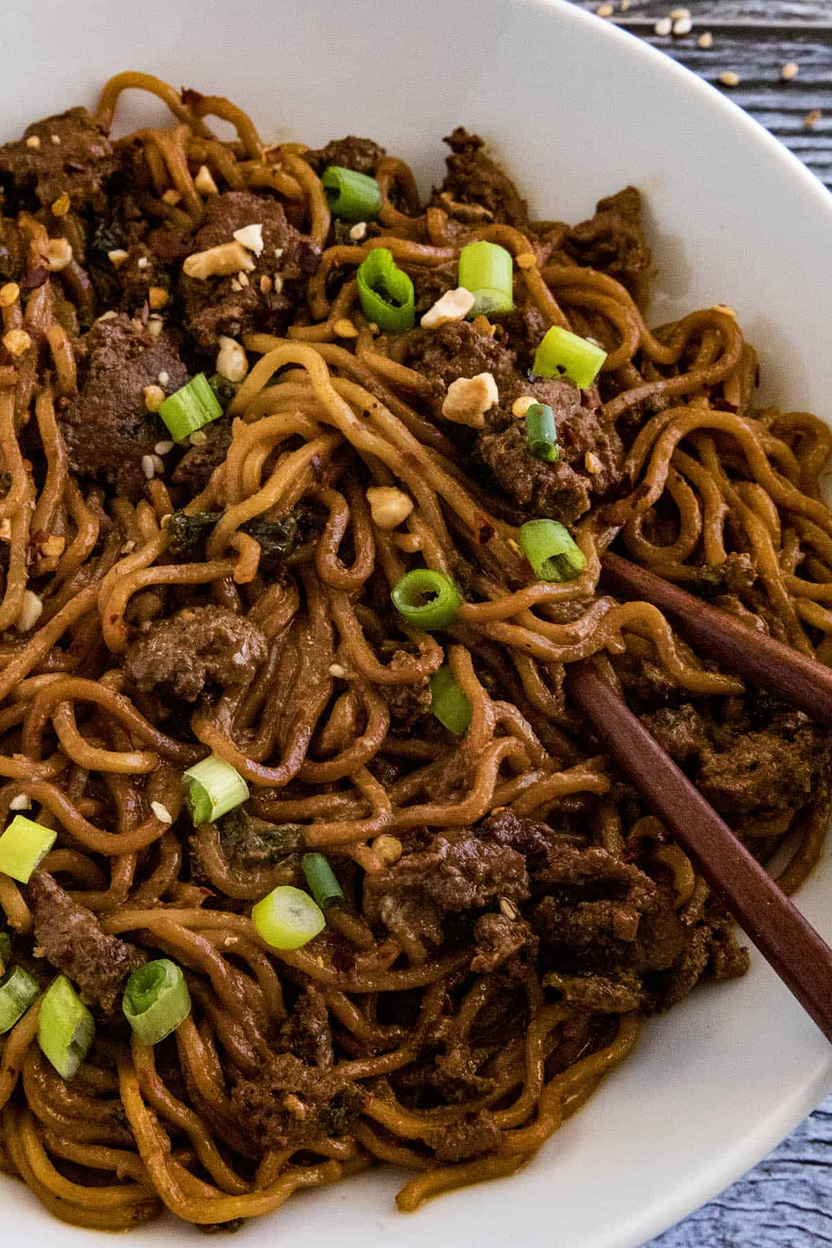 Dan Dan Noodles in a bowl with chopsticks, ready to eat