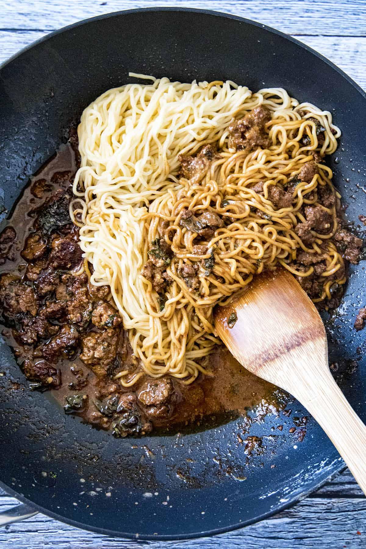 Mixing noodles and dan dan sauce to make dan dan noodles