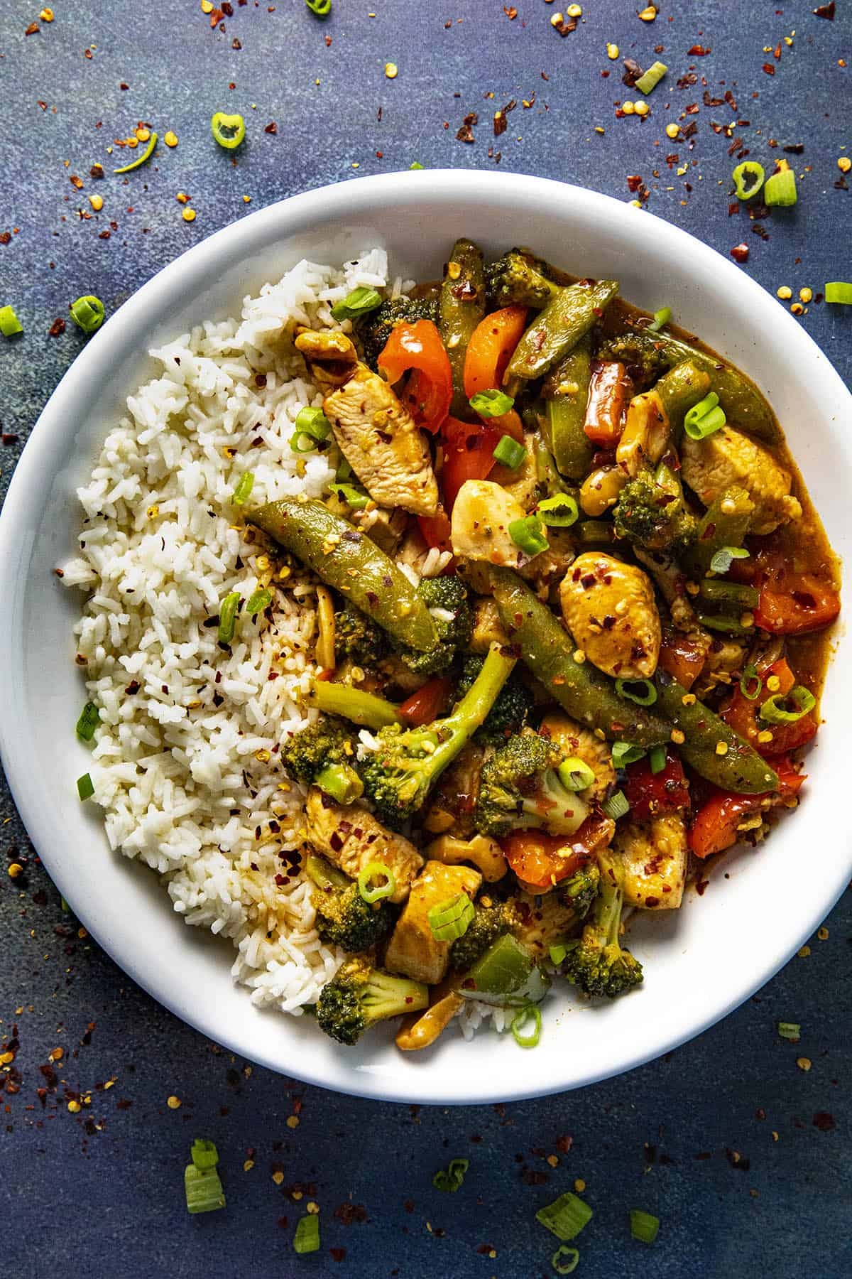 Chicken Stir Fry in a bowl with rice and spicy chili flakes