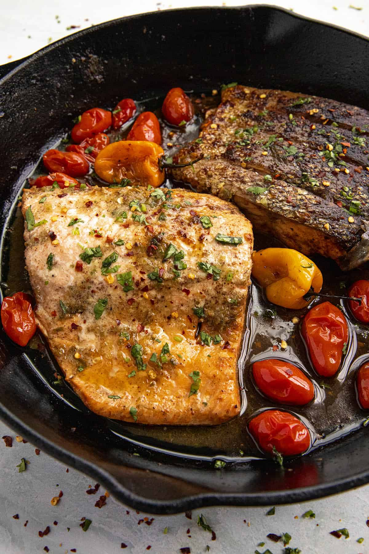 Two pieces of Jerk Salmon in a hot pan with blistered tomatoes and Scotch Bonnet