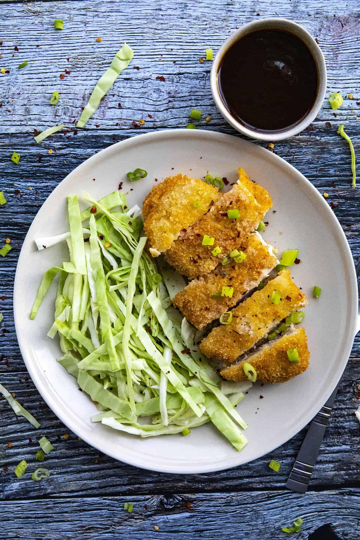 Sliced Pork Katsu on a plate with chopped cabbage