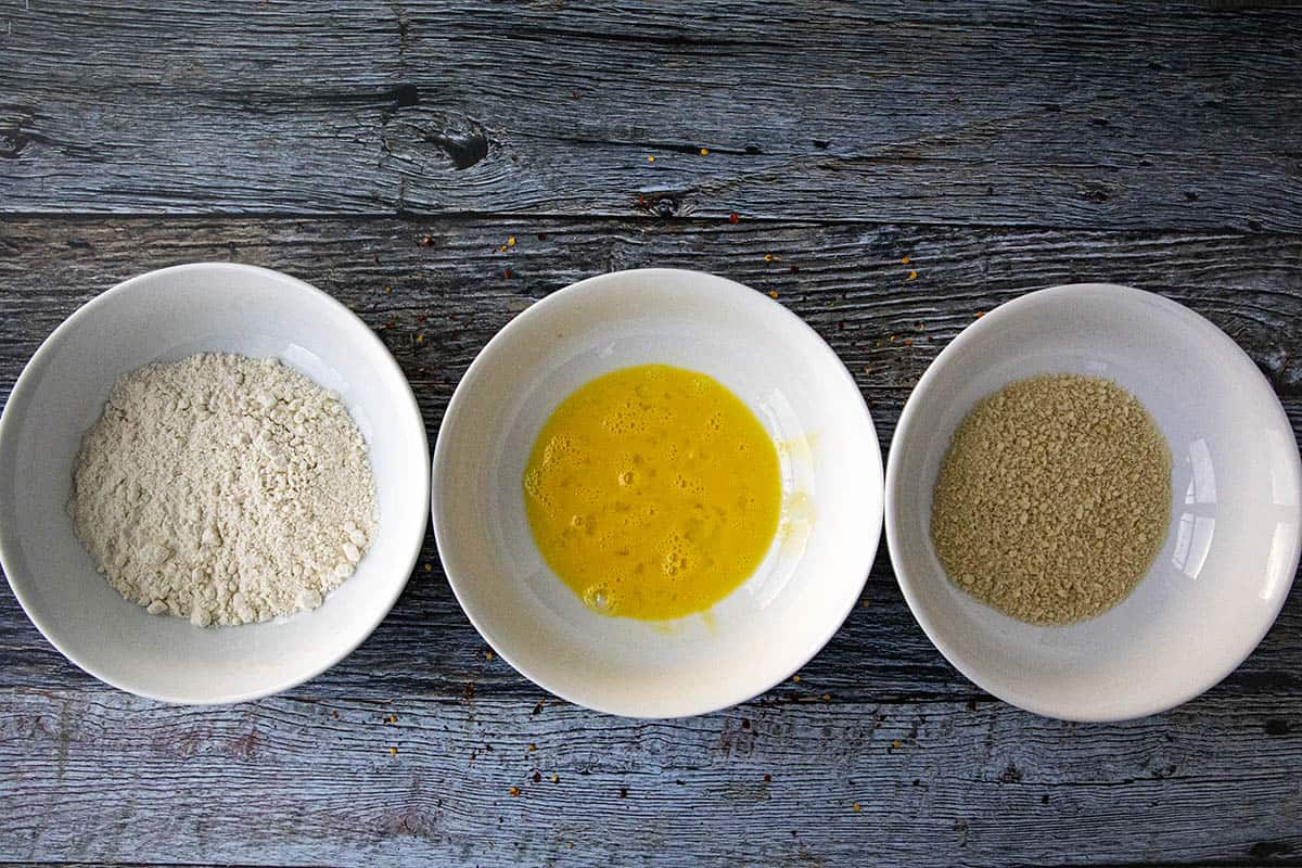 3 bowls set up for making pork katsu, with flour, scrambled egg, and panko