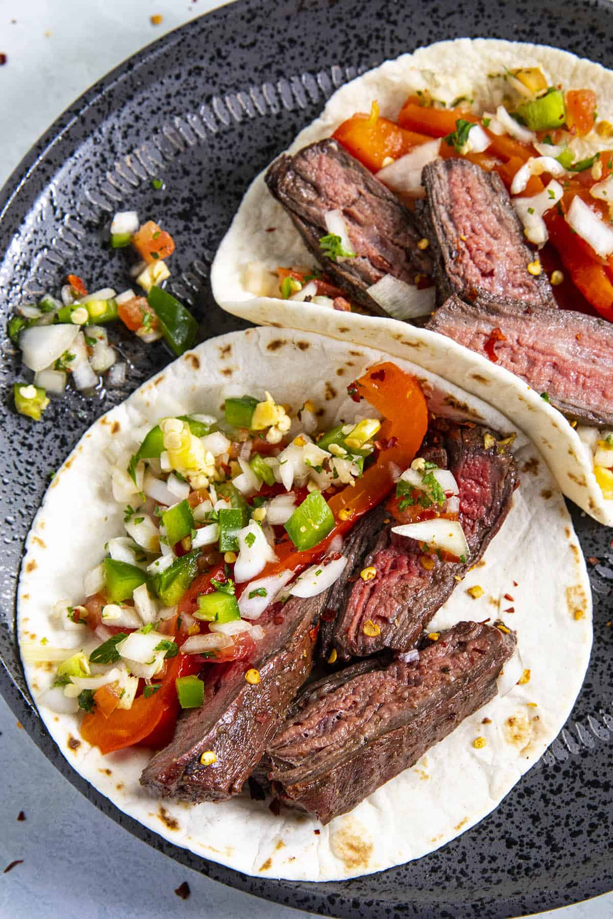 Two charcoal grilled steak tacos with pico de gallo and grilled red pepper