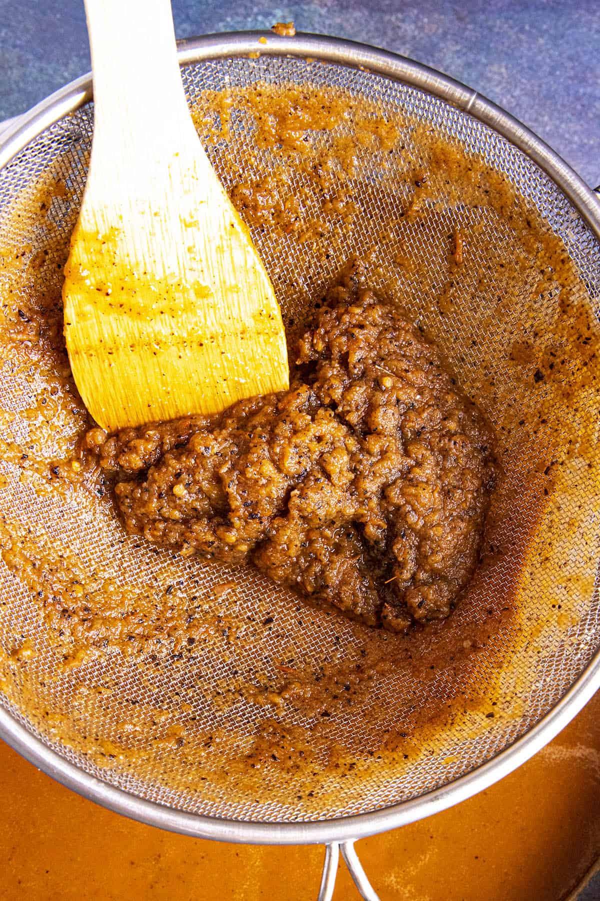 Straining the cooked ingredients to make Tonkatsu Sauce