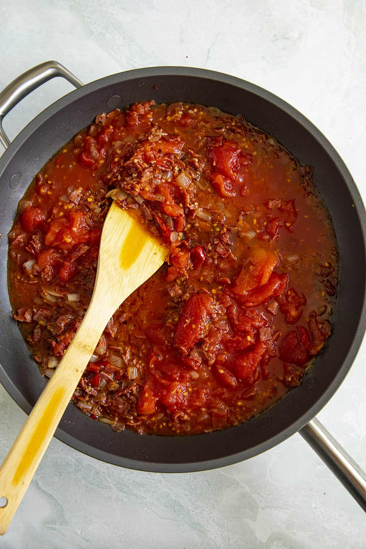 Stirring the Amatriciana sauce in a pan
