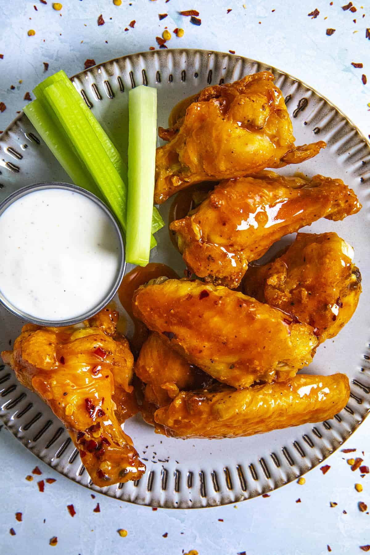 Buffalo Wings on a plate with dressing and celery sticks