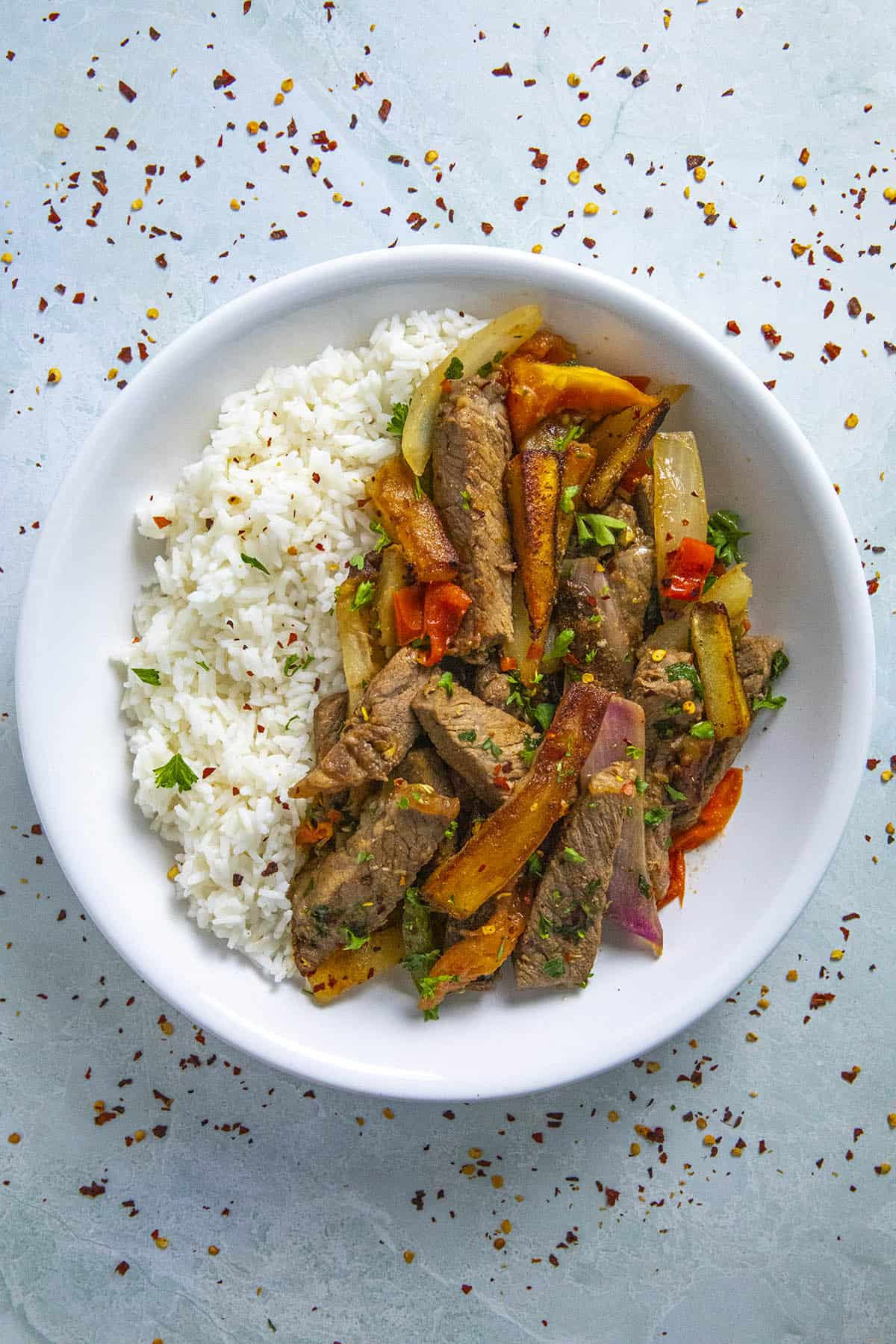 Peruvian Beef Stir Fry with French Fries (Lomo Saltado) in a bow over rice