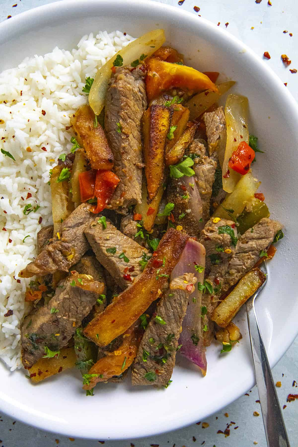Peruvian Beef Stir Fry (Lomo Saltado) in a bow over rice with lots of beef and french fries