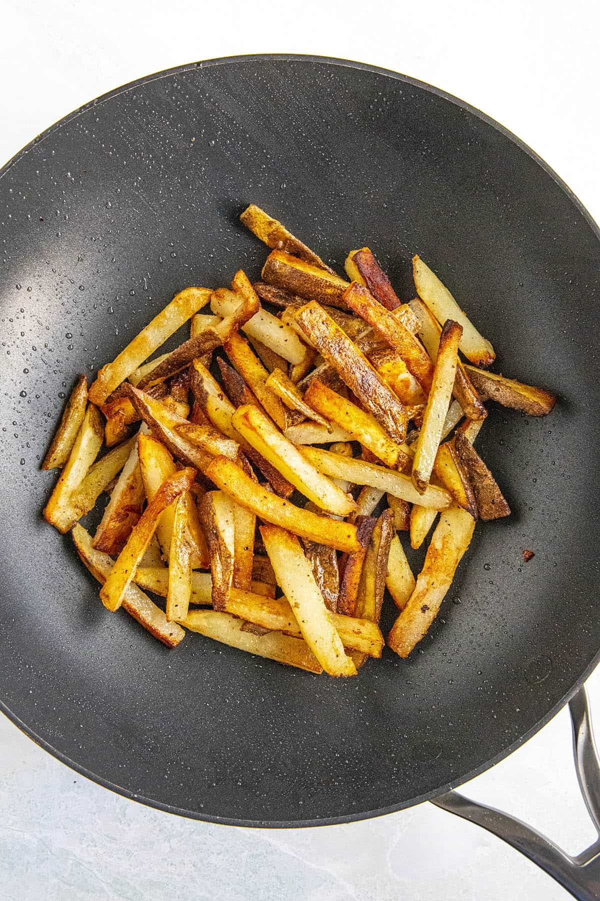Stir frying the french fries in a hot pan with oil