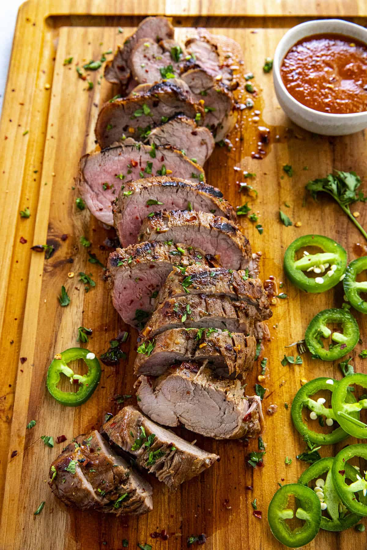 Sliced and grilled marinated pork tenderloin with bbq sauce, ready to serve