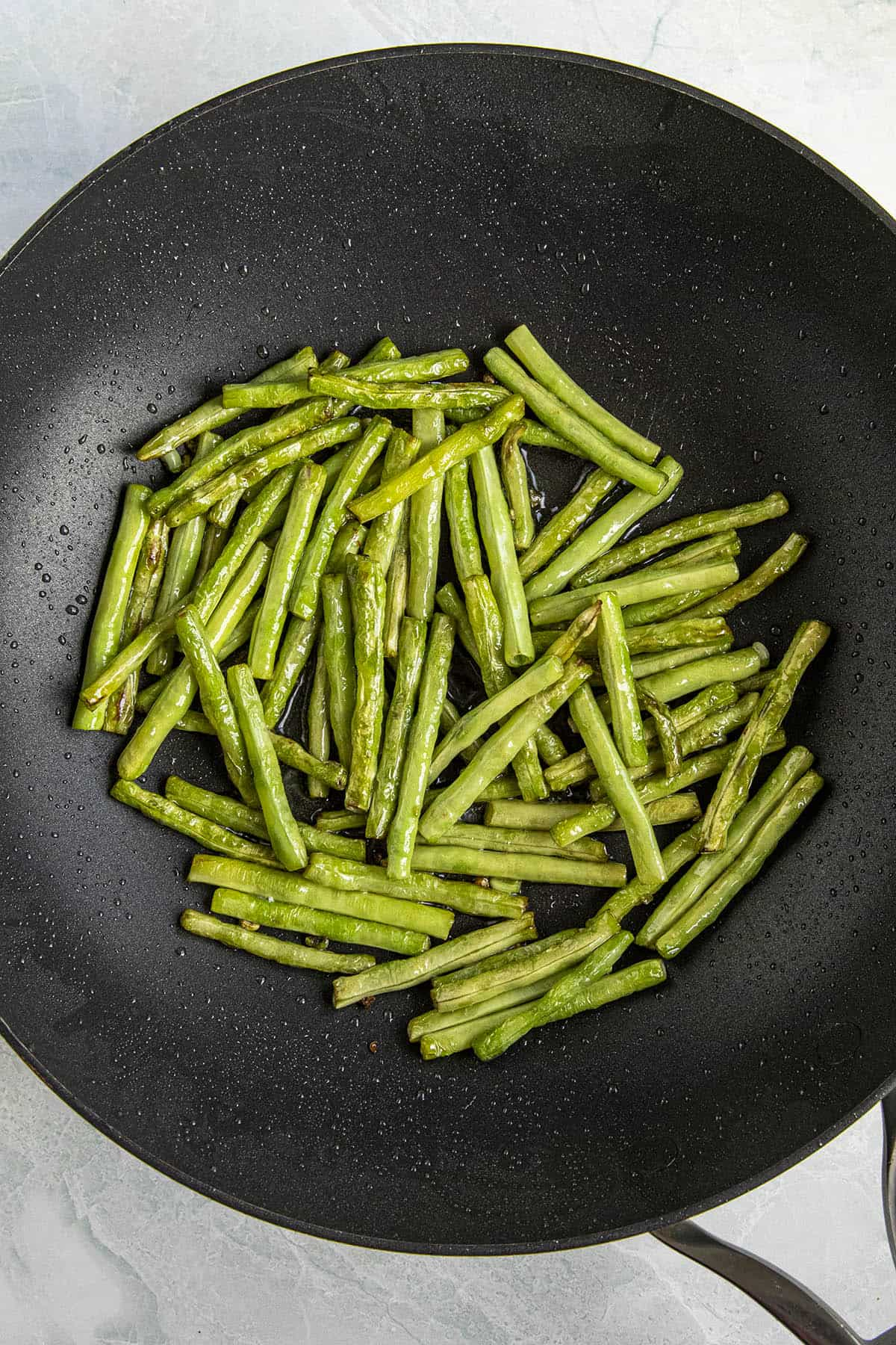 Cooking the long beans in a hot pan