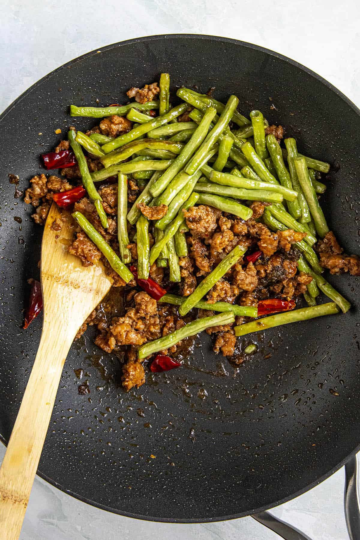 Stirring together the long beans with the pork and peppers in a hot pan