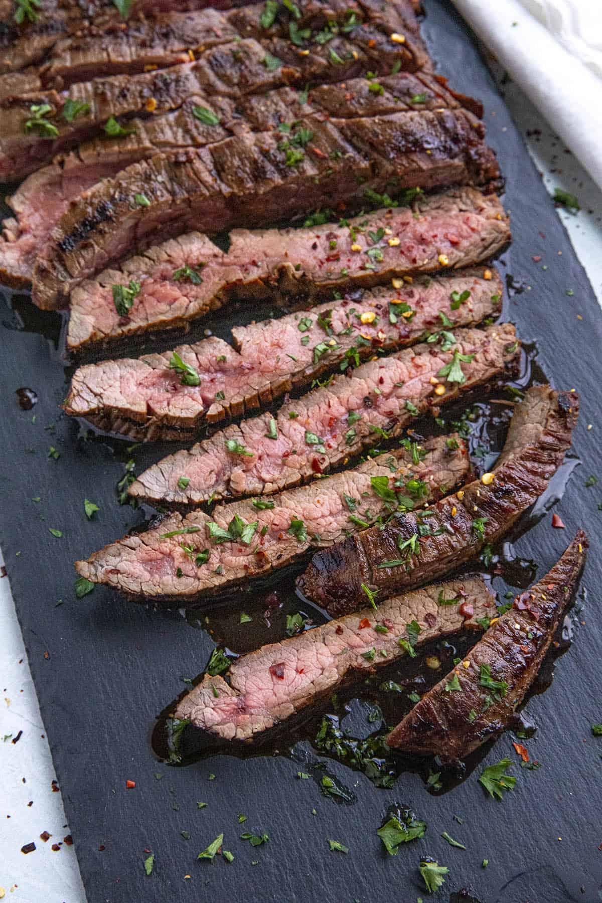 Sliced marinated flank steak on a cutting board