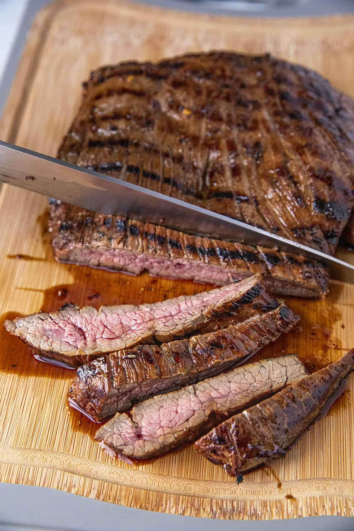 Slicing grilled marinated flank steak across the grain