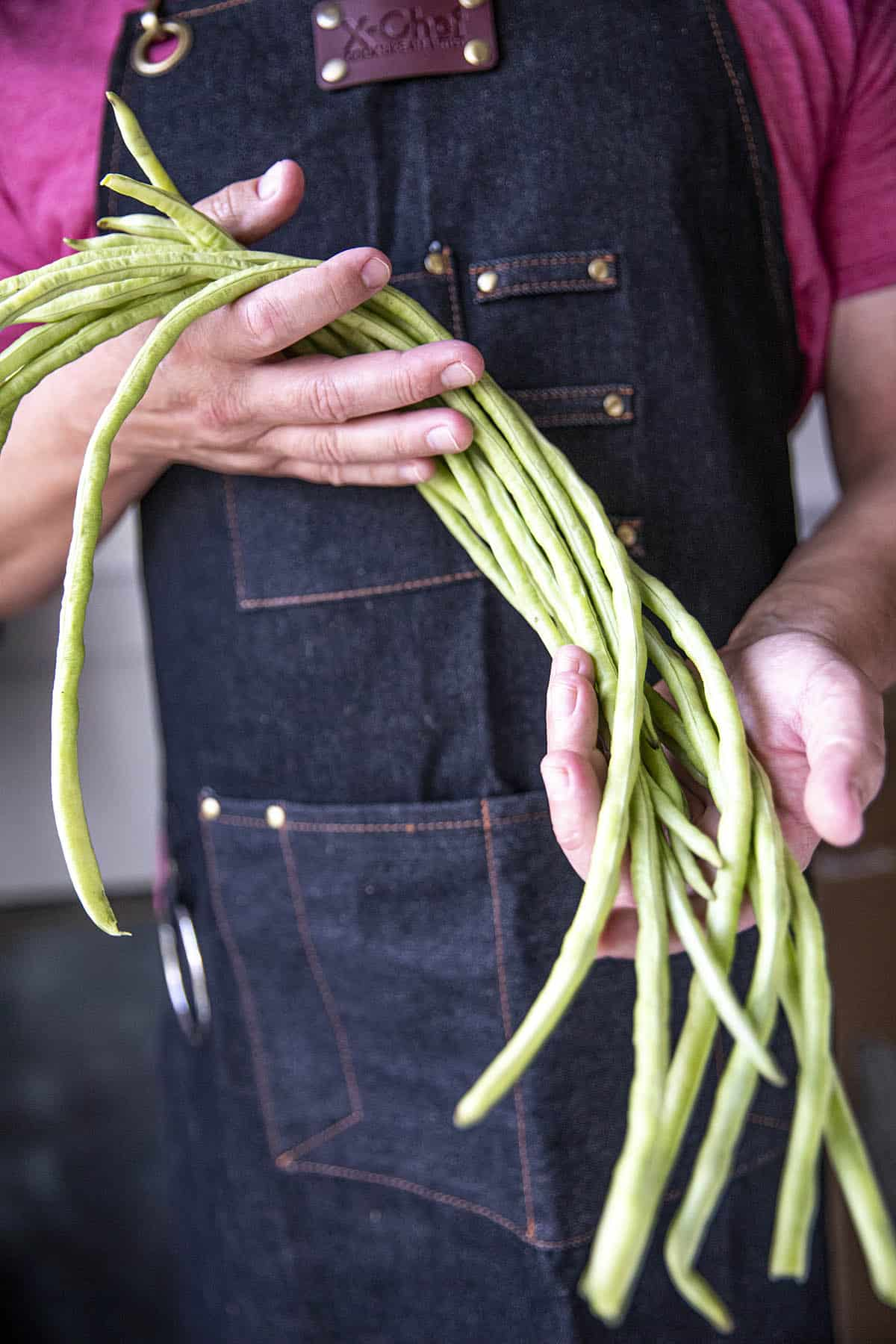 Mike holding a handful of long beans