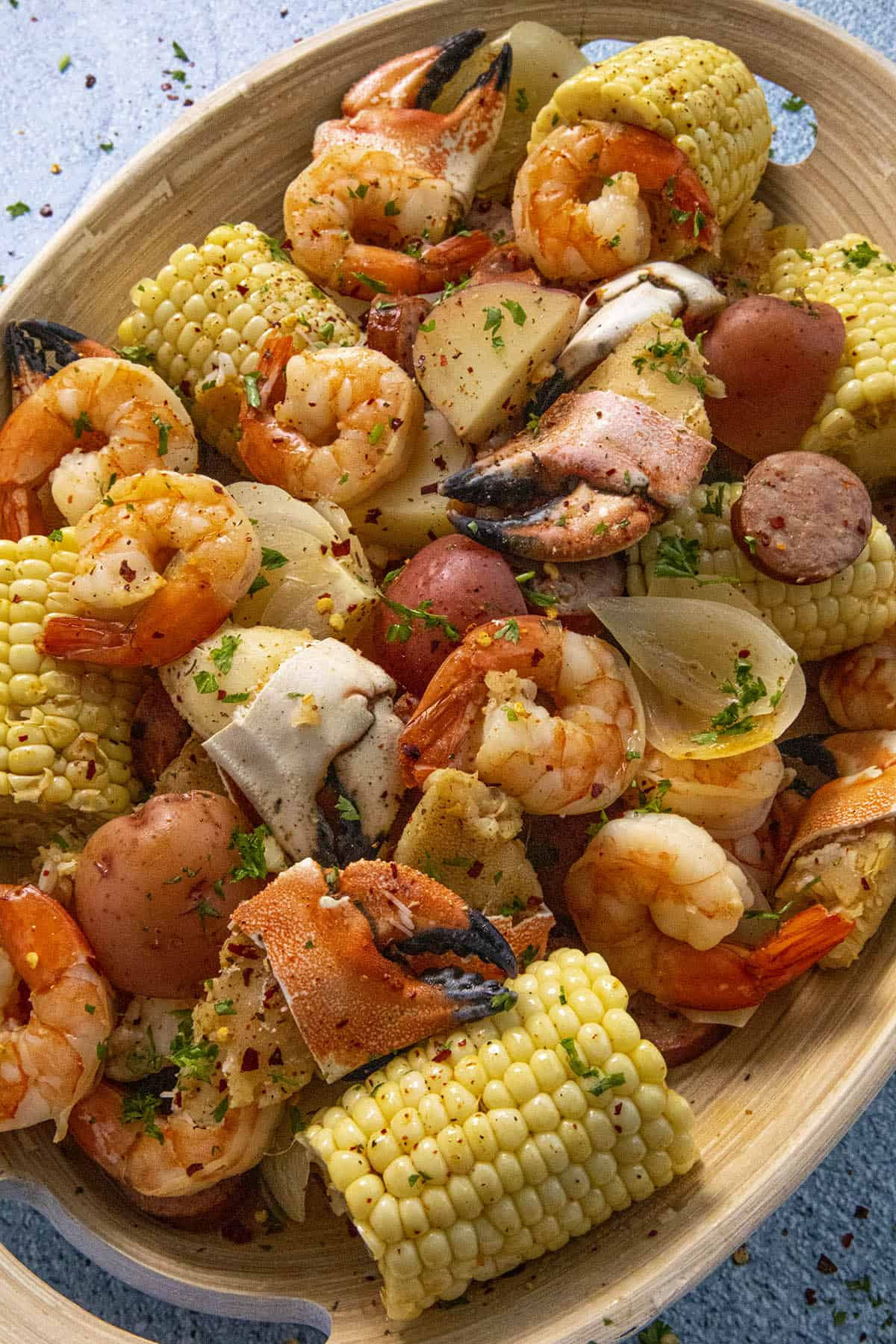 Low Country Boil in a platter with lots of boiled corn, shrimp, crab and smoked sausage