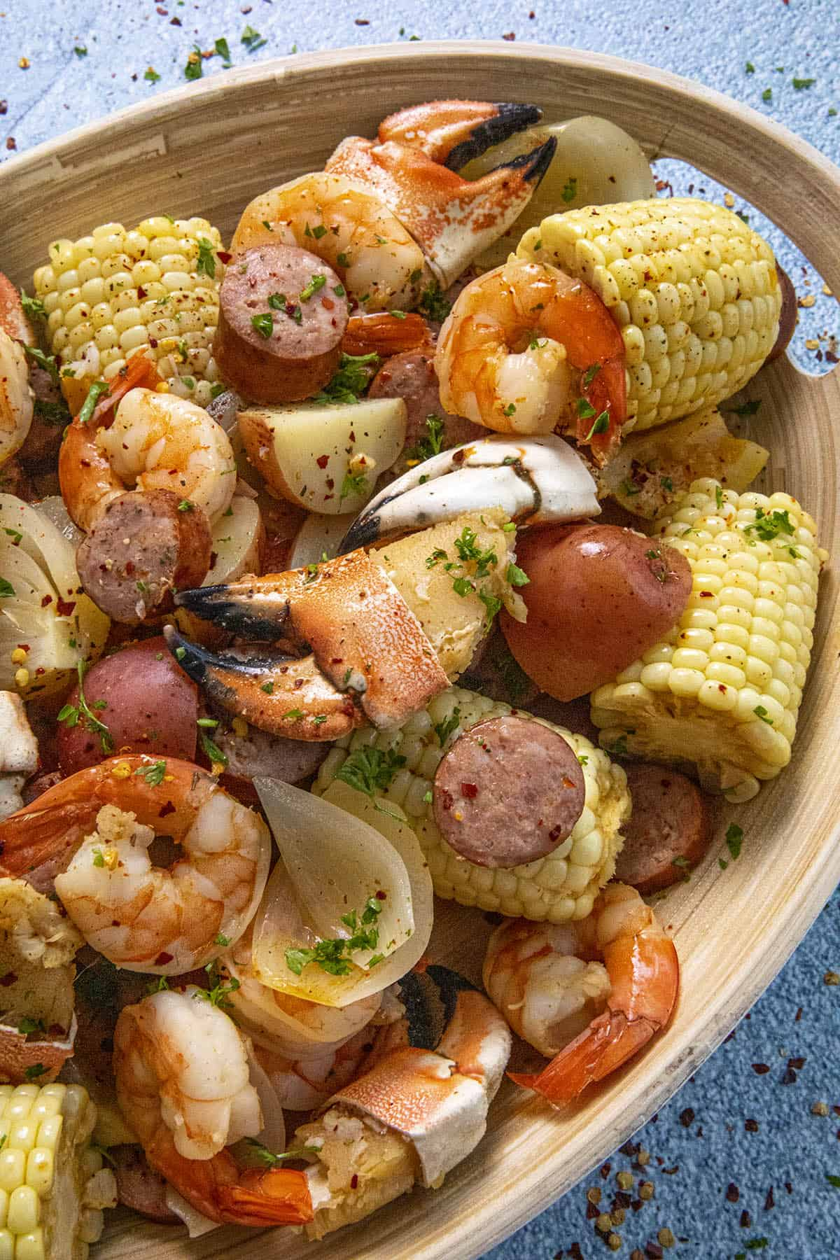 Chunky pieces of seafood, sausage and corn on a platter, low country boil style