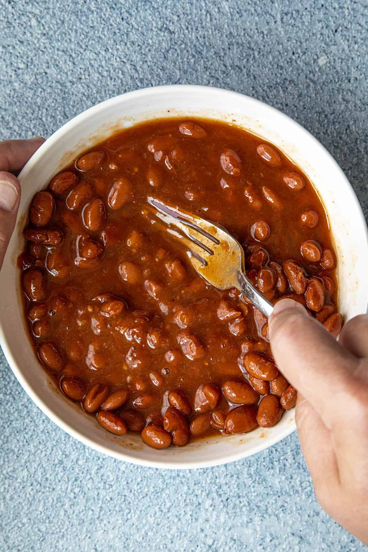 Mashing pinto beans to make a bean burrito