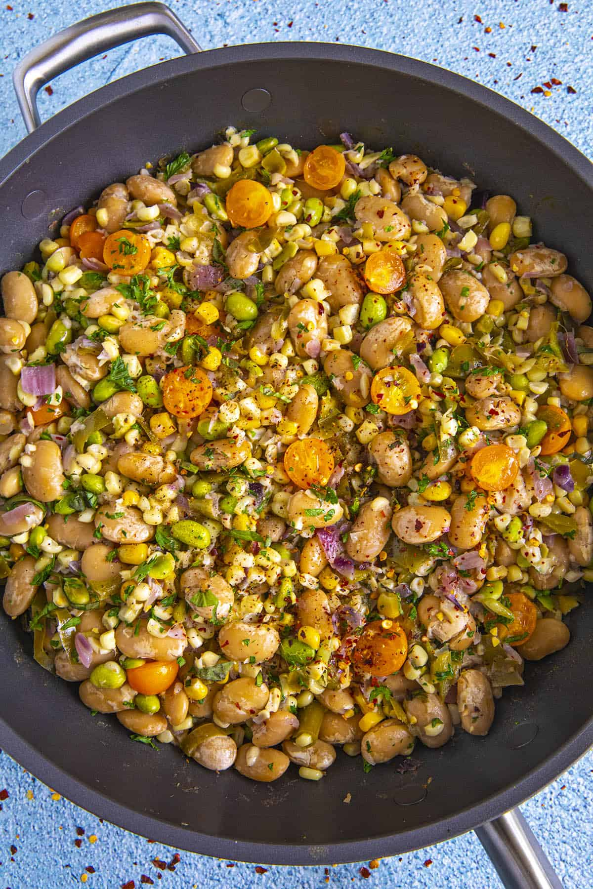 Succotash in a pan with lots of garnish