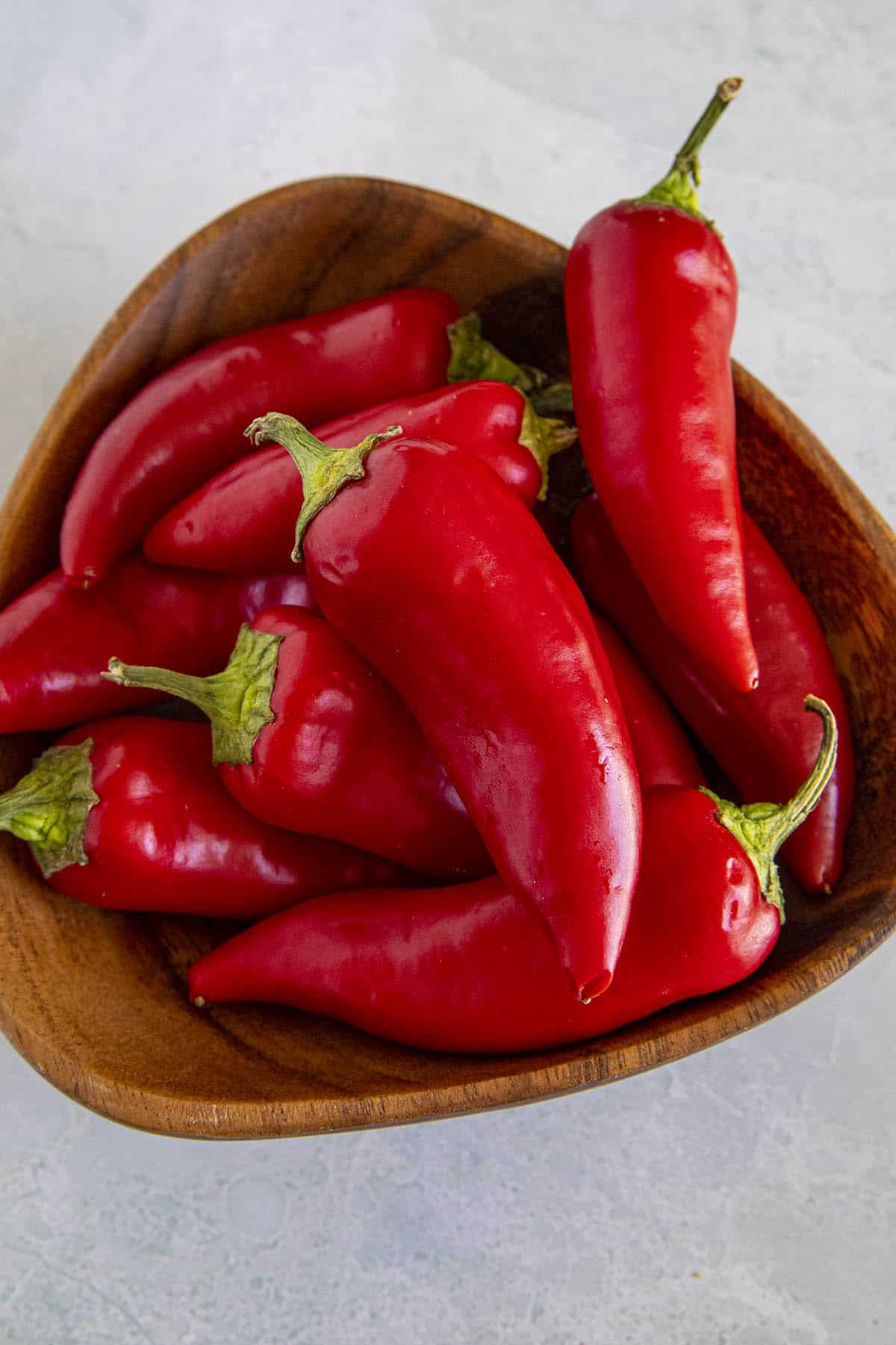 A bunch of spicy Fresno Peppers in a wooden bowl