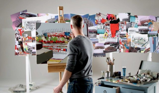 URBAN COLOURS ART REVIEW, PHOTO OF JAMIE THE ARTIST PAINTING A PICTURE WITH OTHER COMPLETED PICTURES AROUND HIM. HE IS STOOD UP WITH ART SUPPLIES TO THE RIGHT OF HIM