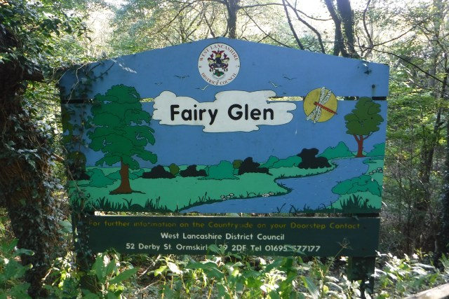 Free days out in Lancashire #mamiadaysout the sign for the fairy glen, a blue sign with green meadow and trees