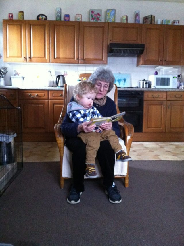 Lucas sat on my Grandmas knee while she reads him a book