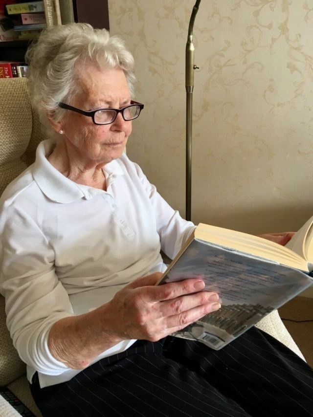 Eyejusters review My Grandma (an elderly lady with grey curly hair) is sat on a chair in a white top and black trousers on wearing purple glasses reading a thick hardback book