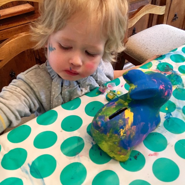 Easter 2018 Lucas is sat at the table with a white a green spotty mat, he is looking down and dipping his paint brush into paint whilst the bunny money box is partly painted next to him