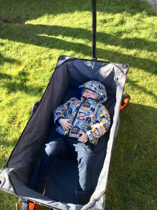 VonHaus camping folding cart review. The camera is looking down at Lucas lying in the camping cart. He has his hood up on his coat which is a superhero pow graphics over it. He is wearing navy pants and the cart is grey. Under the cart you can see grass. It is a sunny day