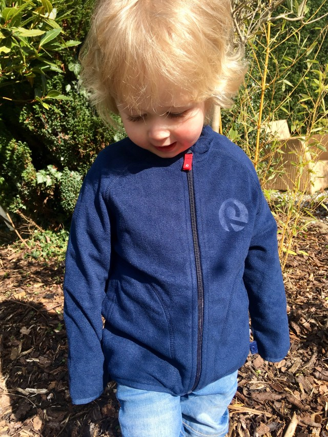 Reima clothing. Lucas is looking down smiling with blonde hair. He is stood in the garden wearing a blue fleece jacket