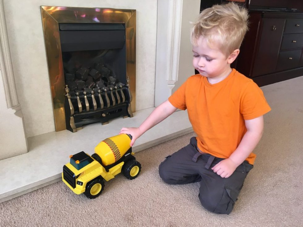 Tonka cement mixer review Lucas is pushing the cement mixer knelt on the carpet with a fire place behind him