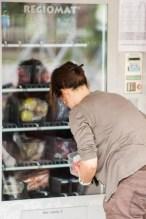 Eine Frau holt die Ware aus dem Ausgabefach