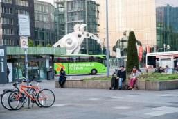 Blick auf die Print-Media-Akademie, die Skulptur. Es fährt ein Flixbus vorbei.