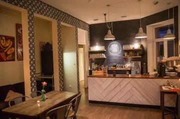 Blick in das Café. Der hintere Bereich, eine Nische und die Theke.