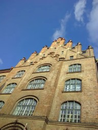 Backsteingebäude, darüber ein blauer Himmel.