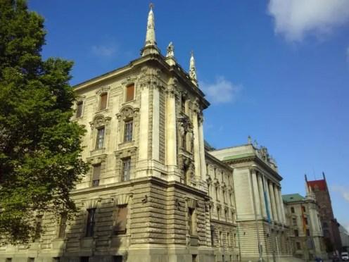 Gebäude mit hohen Säulen und Statuen auf dem Dach.