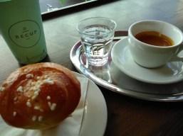 Auf einem Tablett steht ein Flas Wasser mit Espresso und ein Gebäck. Im Hintergrund mein großer Recup-Becher.
