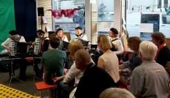 fünf Musiker mit Zieharmonika und Publikum