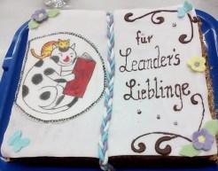 Torte rechteckig mit Zuckerguss. Darauf das Logo des Leanders Leseladen und der Schriftzug für Leanders Lieblinge