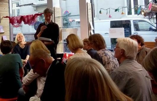 Herr Petermann am Mikrofon, Frau Hoffmann im Hintergrund und Publikum