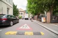 Im Hintergrund ein LKW. Theaterstraße. Auf dem Boden ist ein Vorsicht-Schild mit spielenden Kindern aufgemalt und eine Bodenschwelle.