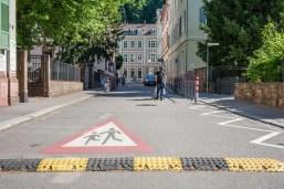 Theaterstraße. Auf dem Boden ist ein Vorsicht-Schild mit spielenden Kindern aufgemalt und eine Bodenschwelle..