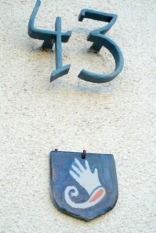 Hausnummer 13 und Handschuh als Wappen am Eingang.